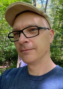 A picture of me in the woods. I'm wearing a white hat, black rimmed glasses, and a blue shirt. I'm gazing into the middle distance.
